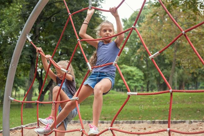 Girls climbing on net ladder