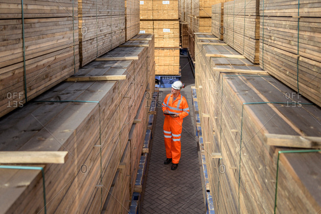 July 23, 2018: Worker among stacks of timber in storage at port