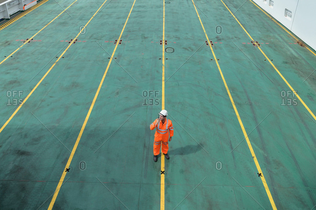 Ship's worker using walkie talkie on deck of ship in port