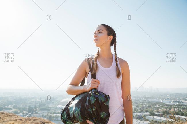 Woman carrying sports bag on hilltop, Los Angeles, US