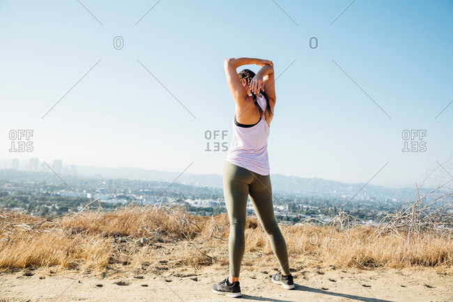 Woman doing stretching exercise on hilltop, Los Angeles, US