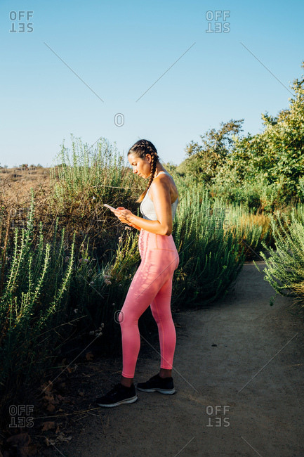 Woman texting among shrubs