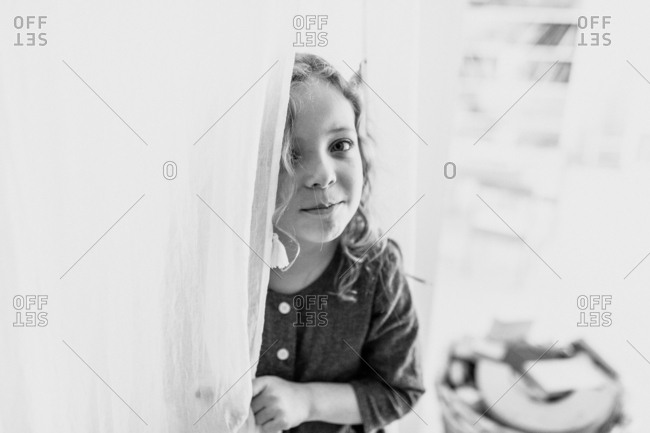 Little girl peeking through curtains
