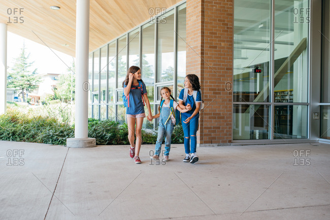 Three sisters holding hands and walking together at school