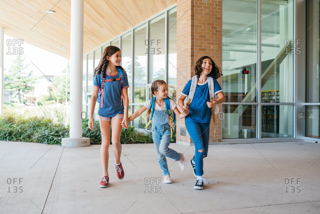 Three girls holding hands while skipping and laughing together at school