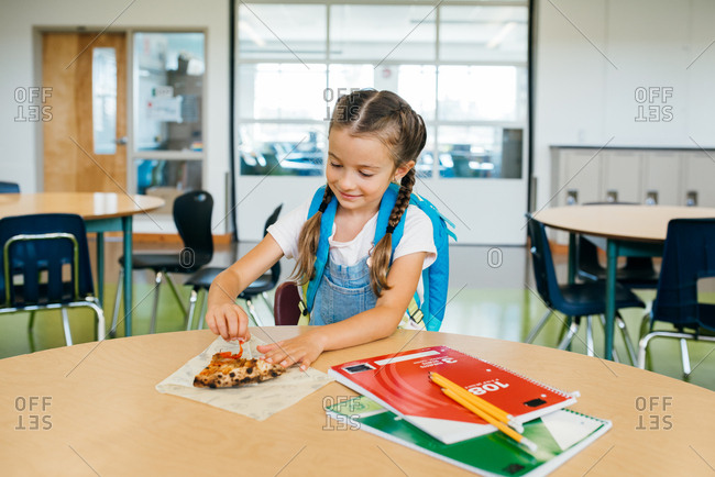 Girl with braided hair having pizza for lunch at school
