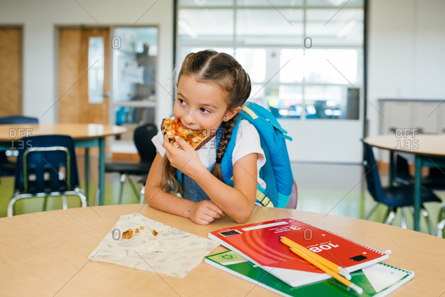 Elementary school student eating pizza for lunch