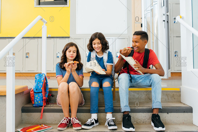 Smiling children sitting on steps and eating pizza together at school
