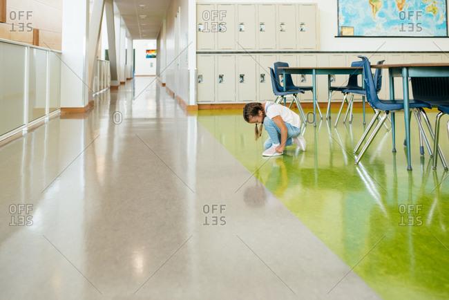Little girl tying shoe in hallway of school