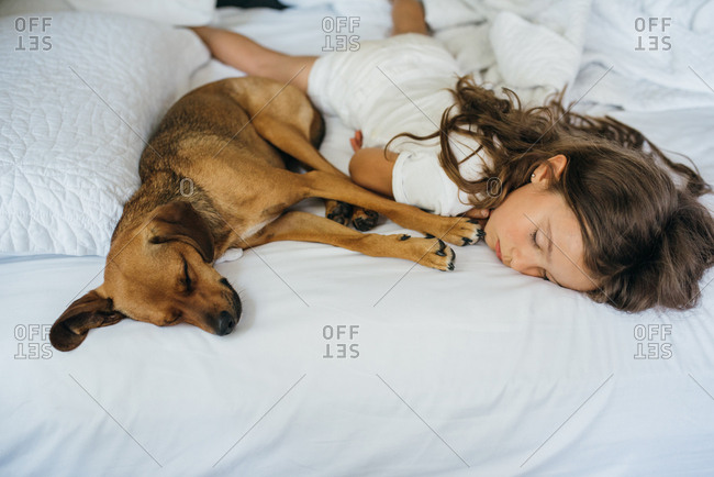 Girl sleeping on the bed with her pet dog