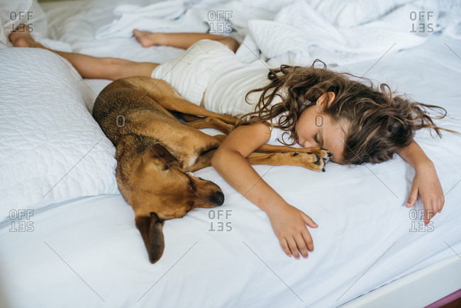 Girl sprawled out on bed sleeping with her pet dog