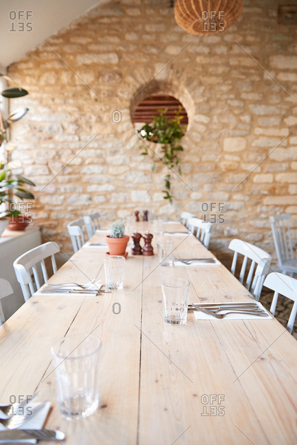 Wooden dining table and chairs in empty restaurant, vertical