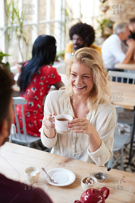 Woman having tea in busy coffee shop with friend, high angle