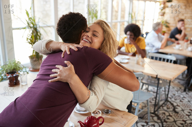 Mixed race couple embracing at the table in a cafe, daytime