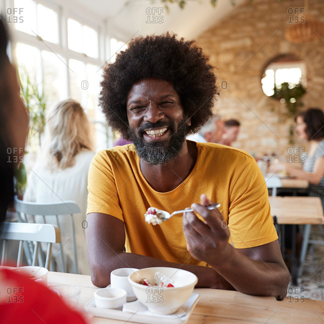 Black man and friend at breakfast in cafe, close up, square