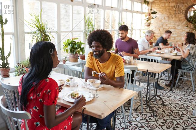 Smiling black couple having breakfast at cafe