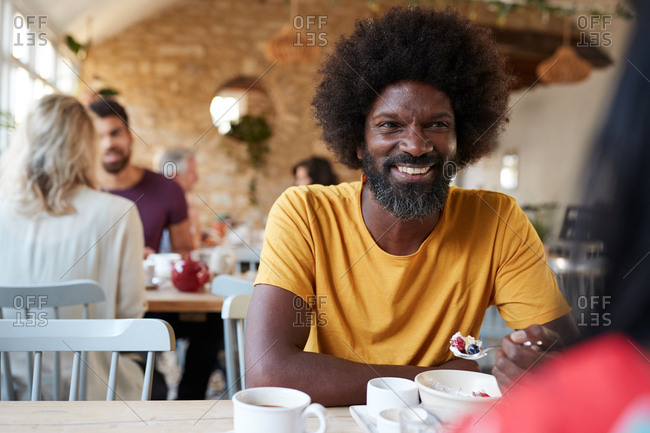 Black man and friend at breakfast in cafe, close up