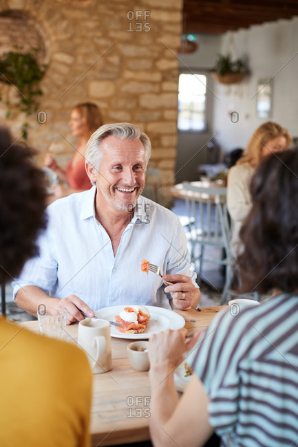 Senior white man at brunch with friends in a cafe, vertical
