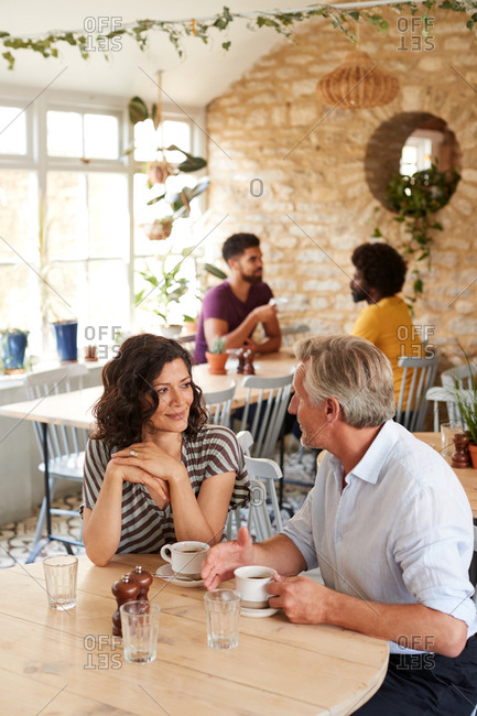 Mature white couple talk over coffee at a cafe, vertical