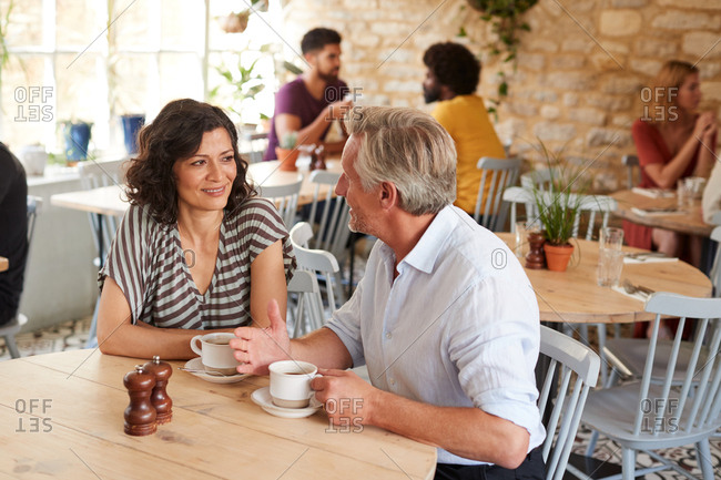 Mature white couple talking over coffee at a cafe, close up