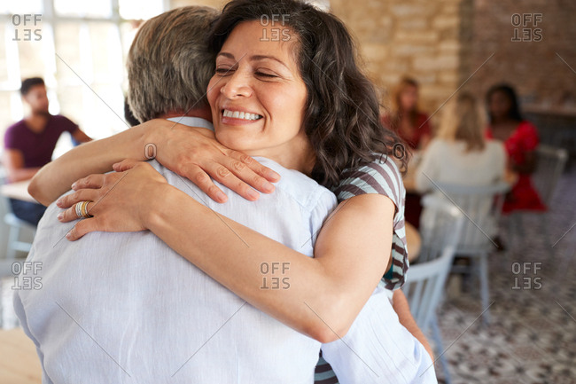 Mature white couple embracing at a cafe, close up