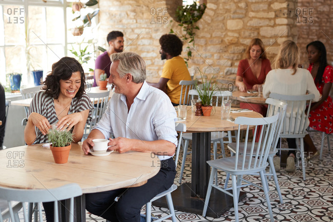 Mature white couple sitting in a cafe laughing, full length