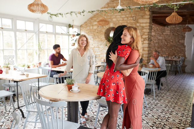 Two female friends embracing at a cafe, side view, close up