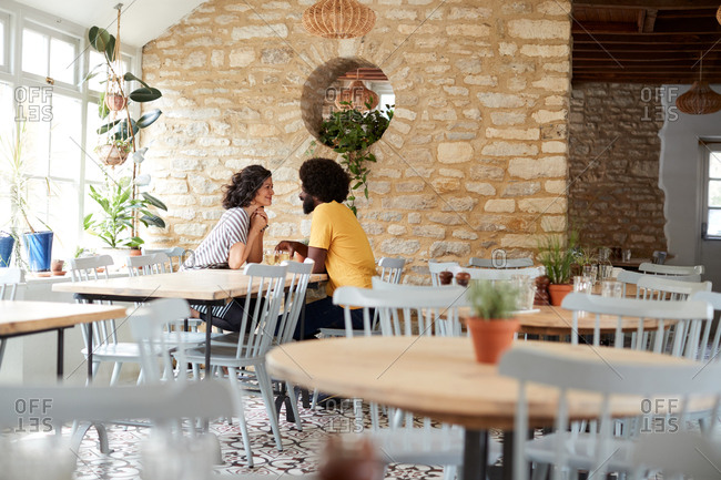 Stone wall, tables and chairs in empty restaurant interior