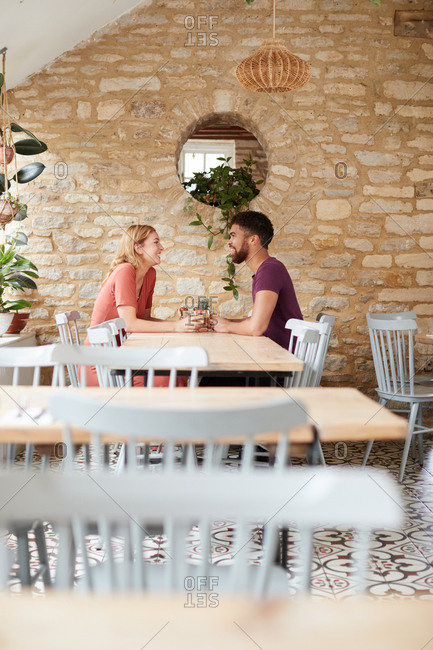 Mixed race couple talking at a table in an empty cafe