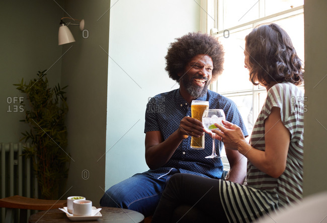 Middle aged couple having a drink on a date in pub, close up