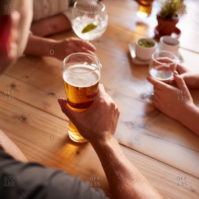 Friends holding drinks on table at a pub, close up, square