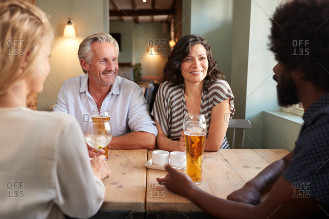 Young couple and an older man drinking at a table in a pub