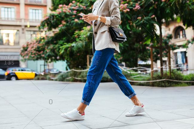 Blonde stylish woman striding across the street.