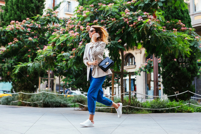 Blonde stylish woman in a hurry running on the street.