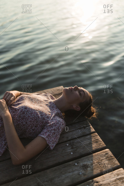 Overhead view of young caucasian girl with a hair bun lying on a dock of a lake in a sunset of a day of summer water background