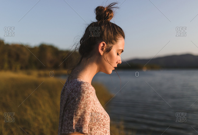 Portrait of young brunette girl with a hair bun observing and relaxing in a lake in a sunset of summer