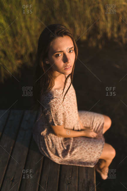 Portrait of young brunette girl with long hair bun observing and relaxing in a lake in a sunset of summer