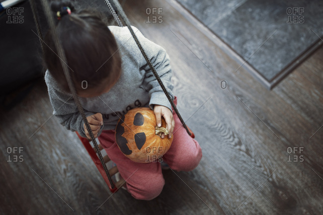 Girl playing with Halloween pumpkin