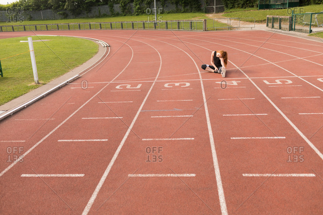 Young female athletic exercising on running track