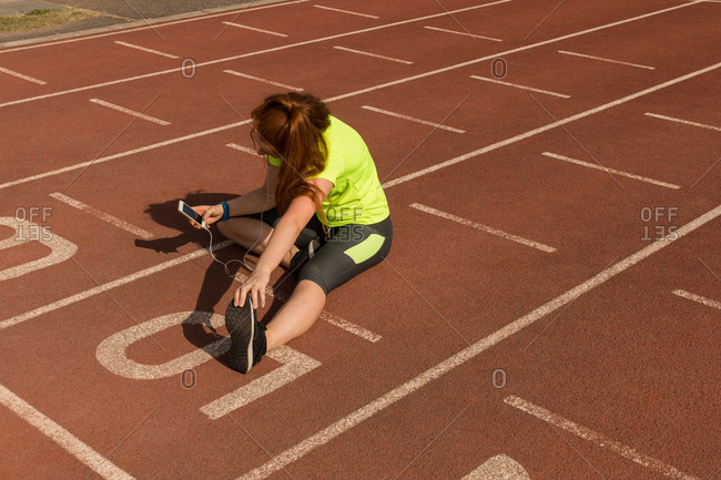 Young female athletic using mobile phone while exercising on running track