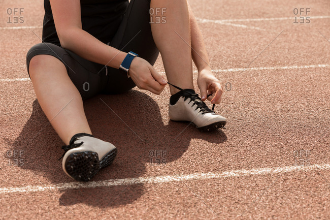 Low section of female athletic tying shoe laces on a running track