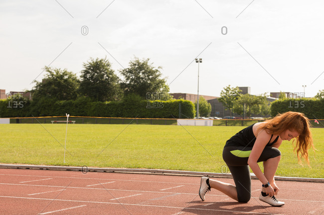Young female athletic tying shoe laces on a running track