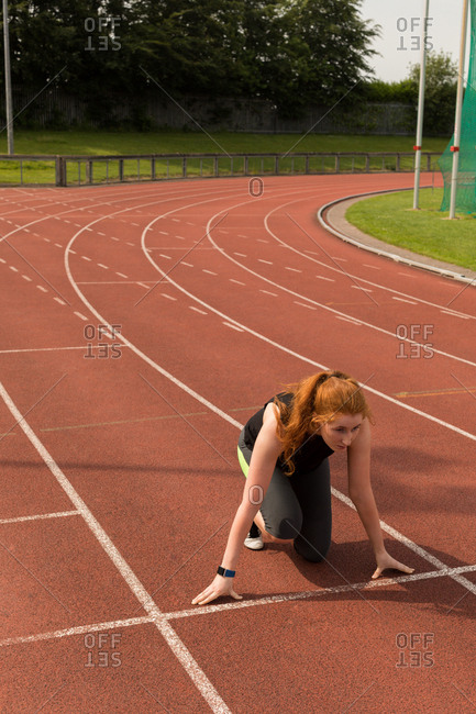 Young female athlete ready to run on running track