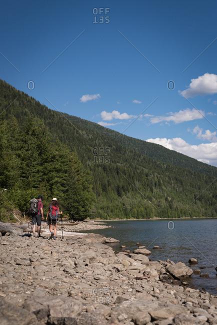 Rear view of couple walking near riverside