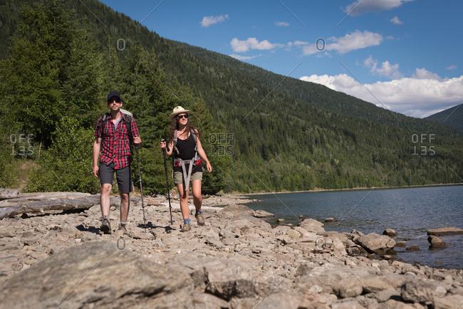 Couple walking near riverside on a sunny day