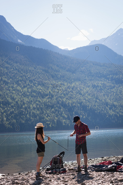 Couple making preparation for setting up a tent on a sunny day