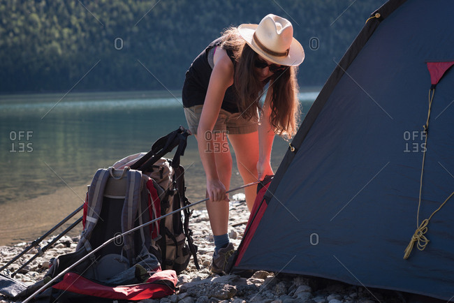 Woman setting up tent on a sunny day