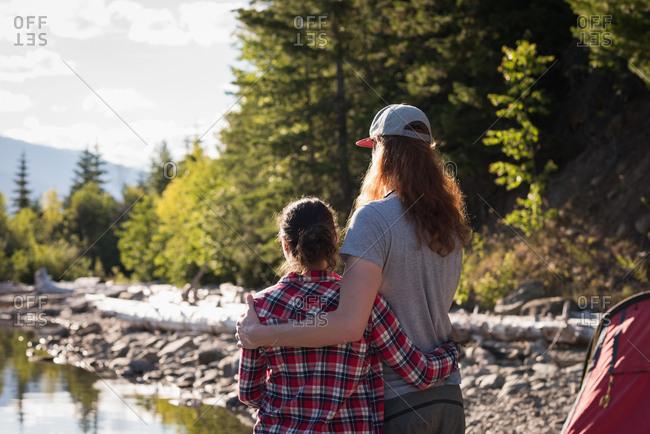 Rear view of couple standing near riverside