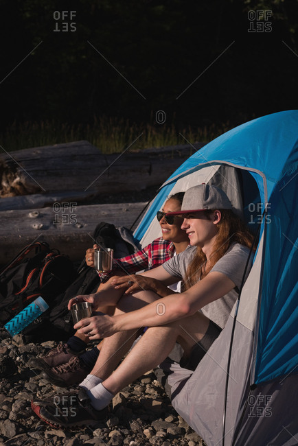 Couple relaxing in tent at countryside on a sunny day