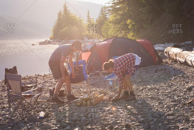 Couple preparing campfire near riverside at countryside